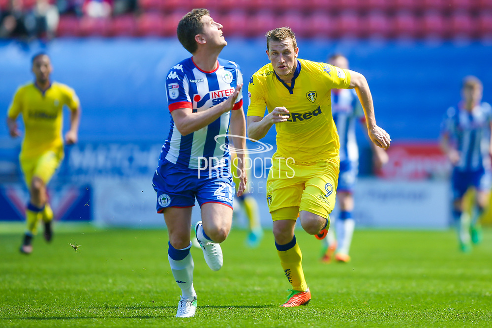 Wigan Athletic  defender, on loan from Hull City, Alex Bruce (21) is chased down by Leeds United forward Chris Wood (9)  during the EFL Sky Bet Championship match between Wigan Athletic and Leeds United at the DW Stadium, Wigan, England on 7 May 2017. Photo by Simon Davies.