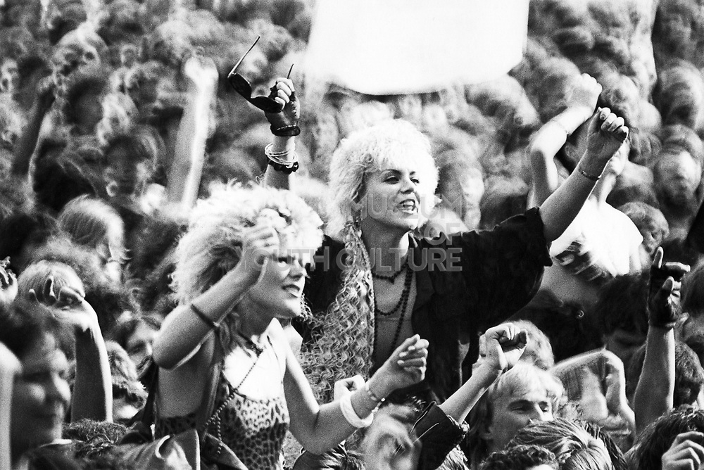 Music crowd scene, Two women on shoulders with arms in air, UK, 1980's