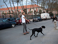 A young man on a skateboard pulled by his dog, at Avenida Ribeira das Naus, downtown Lisbon.This photograph is part of a body of work about Lisbon, feelings, affections and loneliness. Is about a city depressed by the crisis, but even so, tolerant and cosmopolitan. This part of Lisbon, the old town near the river Tejo (Tagus), with his deep character, where local people meets foreigners and alternative ways of life mixes with shamefaced poverty, is sublime by its peculiar light.