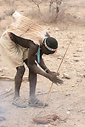 Africa, Tanzania, Lake Eyasi, Hadza men light camp fire by rubbing two sticks together. Small tribe of hunter gatherers AKA Hadzabe Tribe