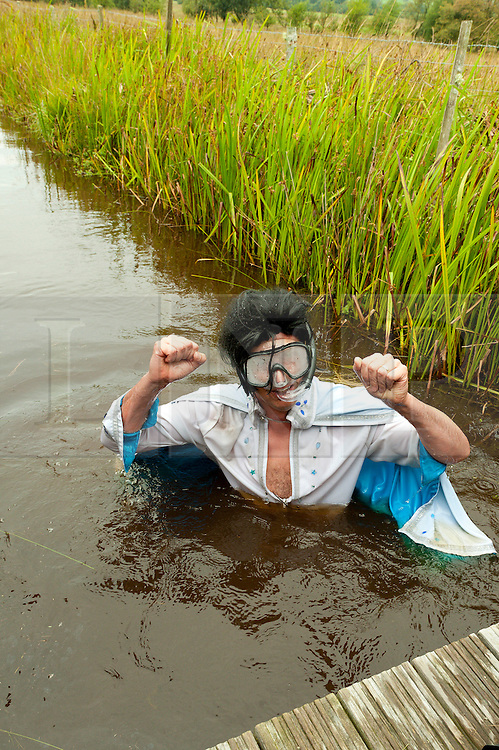 © Licensed to London News Pictures. 30/08/2015. Llanwrtyd Wells, Powys, Wales, UK. Steve Meadows from Leicester dresses as Elvis for the bog event. World Bogsnorkelling Championships, conceived 30 years ago in a Welsh pub by landlord Gordon Green, are held every August Bank Holiday at Waen Rhydd Bog. Using unconventional swimming strokes, participants swim two lengths of a 55 metre trench cut through a peat bog wearing snorkel and flippers. The world record was broken in 2014 by 33 year old Kirsty Johnson from Lightwater, Surrey, in a time of 1 min 22.56 secs. Photo credit: Graham M. Lawrence/LNP