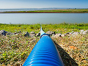 01 JULY 2015 - NONG BUA, LOPBURI, THAILAND:  A water line to draw irrigation and domestic water out of the reservoir at Pa Sak Dam, an agricultural reservoir.  Central Thailand is contending with drought. By one estimate, about 80 percent of Thailand's agricultural land is in drought like conditions and farmers have been told to stop planting new acreage of rice, the area's principal cash crop. Water in reservoirs are below 10 percent of their capacity, a record low. Water in some reservoirs is so low, water no longer flows through the slipways and instead has to be pumped out of the reservoir into irrigation canals. Farmers who have planted their rice crops are pumping water out of the irrigation canals in effort to save their crops. Homes have collapsed in some communities on the Chao Phraya River, the main water source for central Thailand, because water levels are so low the now exposed embankment is collapsing. This is normally the start of the rainy season, but so far there hasn't been any significant rain.    PHOTO BY JACK KURTZ