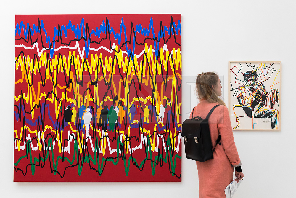 """© Licensed to London News Pictures. 17/05/2019. LONDON, UK. A visitor views """"Le Coeur fait ce qu'il veut Cardiogramme"""", 2014, and """"Jean-Michel (Basquiat)"""", 2018, by Gérard Fromanger at the Draw Art Fair London, the first fair in the UK dedicated to modern and contemporary drawing.  58 international galleries have juxtaposed drawings with related paintings, sculptures, photos or videos, in a ratio of approximately 70% to 30%, using drawing as the core concept.  The inaugural show is open to the public 17 to 19 May 2019 at the Saatchi Gallery in Chelsea.  Photo credit: Stephen Chung/LNP"""
