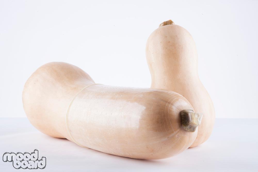 Condom on butternut pumpkin over white background