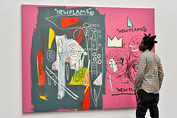 "© Licensed to London News Pictures. 23/06/2017. London, UK. Artist Bradley Theodore views ""New Flame"", 1985, a collaborative work by Andy Warhol and Jean-Michael Basquiat (estimate GBP1.7-2.2m) at the preview of Sotheby's Contemporary Art Sale in New Bond Street.  The auction, which is dominated by Pop art, takes place on 28 June. Photo credit : Stephen Chung/LNP"