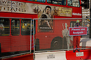 Passing red bus featuring Wrath of the Titans movie ad and scaled human workman figure who warns pedestrians to stay on established footpath, and not wander into construction site roadways.