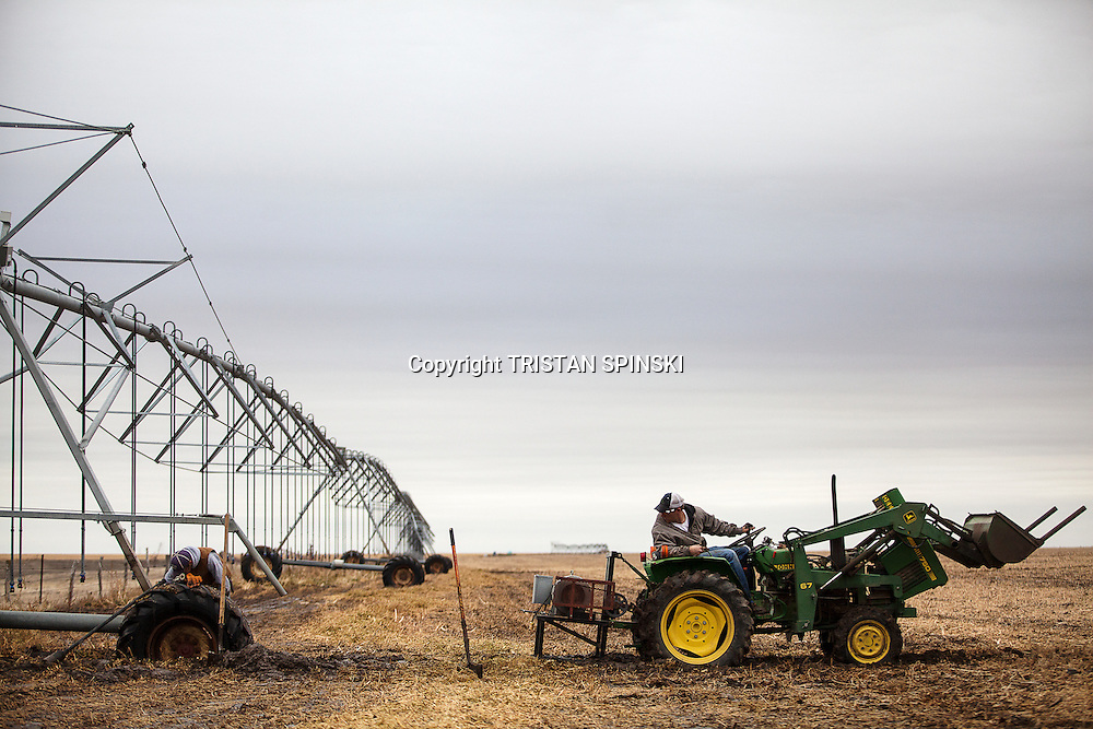 Brett Oelke, right, tries to pull out a center pivot irrigation system that has become stuck in the mud on his family's 6,000-acre farm outside of Hoxie, Kan., on Friday, Oct. 12, 2012. As historically dry conditions continue, farmers from South Dakota to the Texas panhandle rely on the Ogallala Aquifer, the largest underground aquifer in the United States, to irrigate crops. After decades of use, the falling water level ? accelerated by historic drought conditions over the last two years ? is putting pressure on farmers to ease usage or risk becoming the last generation to grow crops on the land. Farmers like Mitchell Baalman (not pictured) and Brett Oelke are part of a farming community in in Sheridan County, Kansas, an agricultural hub in western Kansas, who have agreed to cut back on water use for crop irrigation so that their children and future generations can continue to farm and sustain themselves on the High Plains.