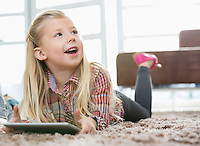 Cute girl with digital tablet looking away while lying on rug in living room