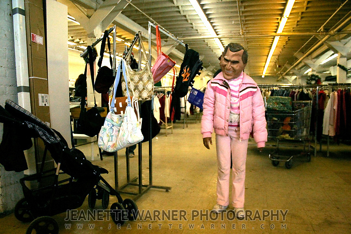 A girl hides behind a mask of George Bush in a good-will store in Rochester, New York.