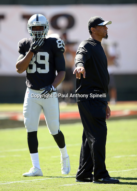 Oakland Raiders wide receiver Amari Cooper (89) looks on as Oakland Raiders assistant defensive backs coach Rod Woodson points while the team warms up before the 2015 NFL week 5 regular season football game against the Denver Broncos on Sunday, Oct. 11, 2015 in Oakland, Calif. The Broncos won the game 16-10. (©Paul Anthony Spinelli)