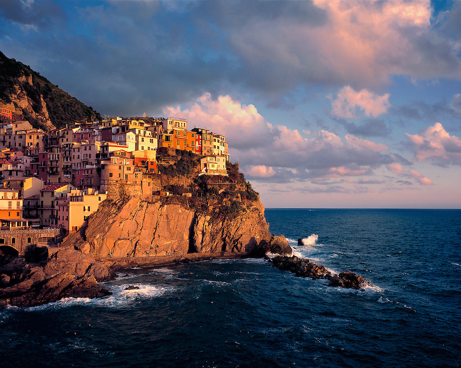 Late afternoon light bathes the colorful walls of Manarola, one of five villages that make up Italy's Cinque Terre National Park, on the Ligurian Coast of Italy.
