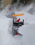 A man shovels and uses a snow blower Wednesday, Feb. 2, 2011, in Milwaukee, Wi. The area was under a blizzard warning and some freeways were shut down. (AP Photo/Jeffrey Phelps)