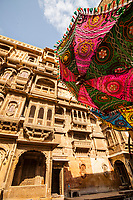 One of the many amazing Havelis in Jaisalmer, Rajasthan, India and a parasol adorned with decorations.