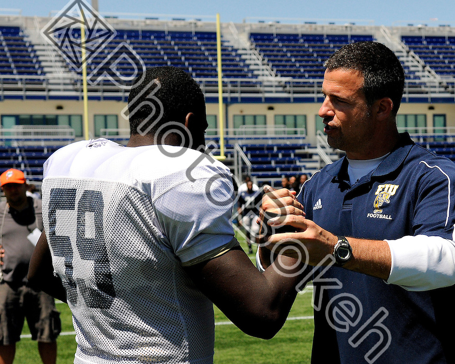 2011 April 4 - Florida International offensive lineman Donald Senat receiving his Sunbelt Championship ring from head coach Mario Cristobal for the victory during the Little Caesars bowl. Florida International University football offense defeated the defense in the annual Blue and Gold Spring Game, 19-10, at FIU Stadium, Miami, Florida. (Photo by: www.photobokeh.com / Alex J. Hernandez)