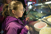 Lauren Kelley, 6, of Fairport, watches as her ice cream donut is prepared at the seventh annual Ice Cream for Breakfast fundraiser at Moonlight Creamery in Fairport on Saturday, February 7, 2015.