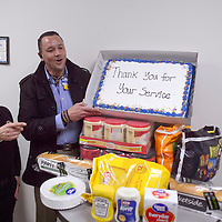 Jeremy Hocker, from Walmart on the right, presents Roberta Jaramillo and the staff at MCKinley County Sheriff's office in Gallup complimentary food Wednesday for a belated gift for National Officer's Appreciation Day January 9.