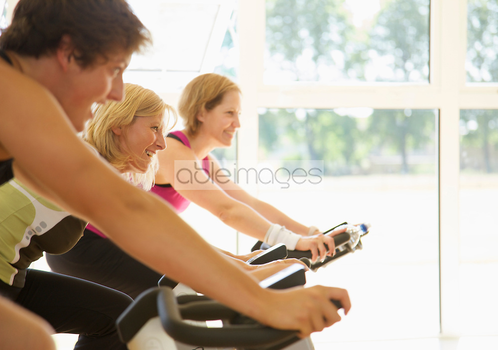 Close up of a group of people cycling on gym bikes