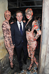 GUY PELLY and waitresses at the launch party for the new nightclub Tonteria, 7-12 Sloane Square, London on 25th October 2012.
