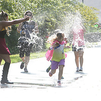 Alexis Bell, left and Paisley Murff splash runners with water balloons during the Super Hero Fun Run Saturday July 26, 2014 at the Myrtle Grove Library in Wilmington, N.C. (Jason A. Frizzelle)