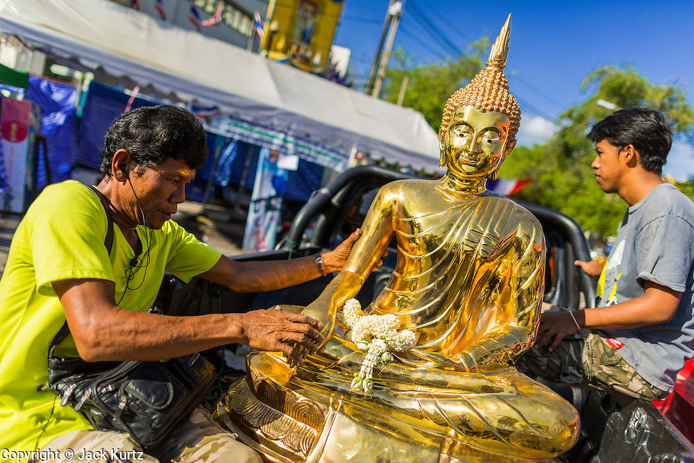 "23 MAY 2014 - BANGKOK, THAILAND:  Anti-government ""Yellow Shirts"" move a Buddha statue away from the anti-government protest site after the Thai army ordered the site closed. The Thai military seized power in a coup Thursday evening. They suspended the constitution and ended civilian rule. This is the 2nd coup in Thailand since 2006 and at least the 12th since 1932.   PHOTO BY JACK KURTZ"