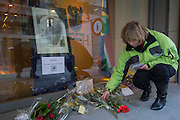 Brussels Belgium 6th December 2013. At the South African Embassy in Brussels people gather, Nelson Mandela died just yesterday.A woman puts flowers at the tribute outside