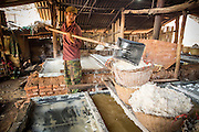 13 MARCH 2013 - BOTEN, LUANG NAMTHA, LAOS:  A man shovels salt into a basket in a salt factory in Boten, Laos. Salt in Boten is made by boiling briny water and collecting the salt that is left behind. The salt wells in Boten, Laos, just south of the Chinese border, have brought a measure of fame to the area for centuries. French forces asserted French dominance over the region in 1894 to control the salt trade. Some of the salt works face an uncertain future because of economic development from China. The area is being developed into a huge parking lot to accommodate truck and tourist traffic into and out of China. PHOTO BY JACK KURTZ