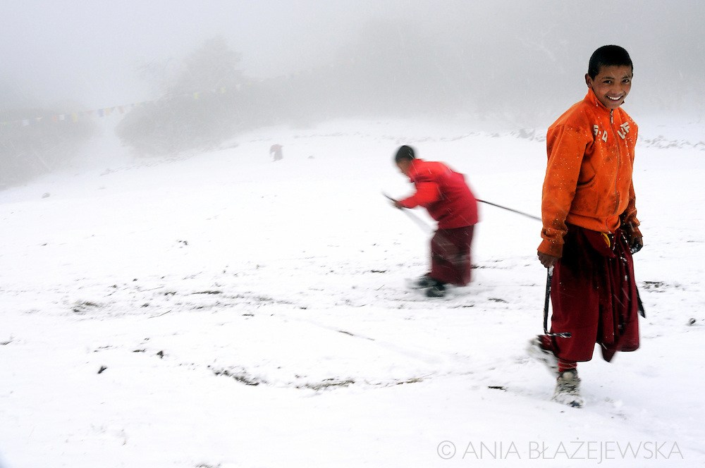 Nepal, Tengboche. Buddhist monks playing and skiing on snow in the monastery area.