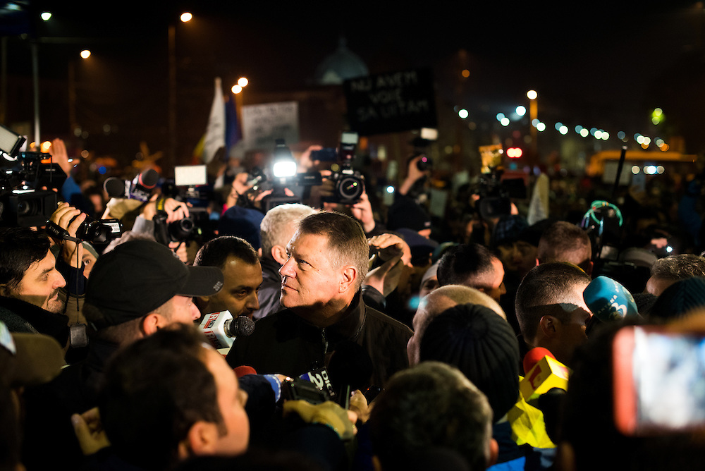 President Klaus Iohannis is mobbed by protesters and media while making an unannounced visit to University Square on November 8, 2015 in Bucharest, Romania.