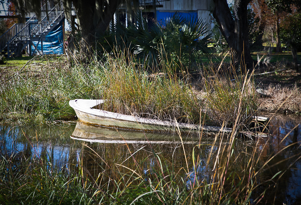 Boat filled with grass on Isle de Jean Charles.  The Isle de Jean Charles is losing land at a quick pace.