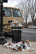Due to the volume of pedestrian traffic walking from Union Station toward the National Mall for the Presidential Inauguration, a public trash can overflows its capacity.<br />