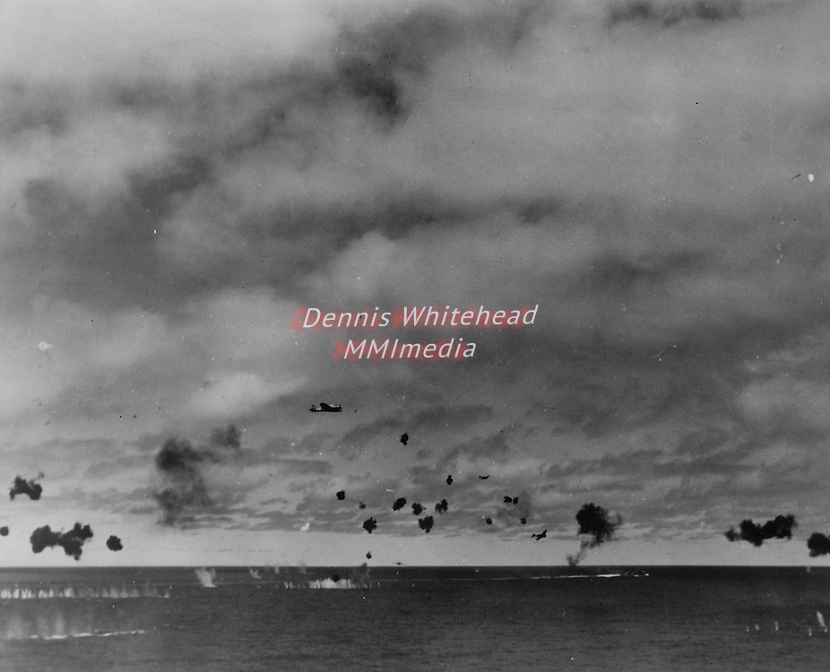 June 3-6, 1942 - Japanese planes, flying through heavy anti-aircraft fire, attack ships of the Pacific Fleet in the Battle of Midway Island. Smoke on horizon is from a downed plane. Splashes in foreground are caused by falling shrapnel.