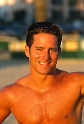 Handsome shirtless smiling man during a sunset