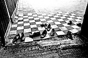In the mosque doorway, 5 pairs of shoes scattered anyhow just outside.  A tattered straw carpet in front, a tile floor beyond made of black and white tiles in a checkered pattern.  The disorder of the shoes and the orderliness of the tiles form a striking contrast.