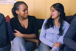 Two teenage girls sitting together smiling,