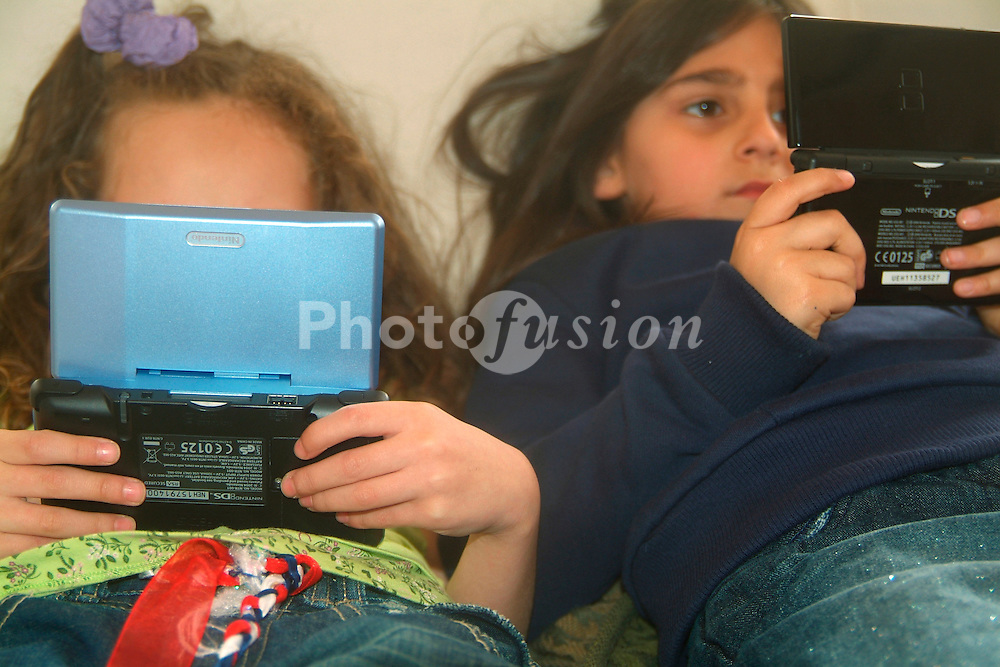 Girls playing with Nintendo DS game console UK