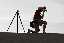 Silhouette of an adult male photographer with tripod and camera, Sand dunes, Mesquite Dunes, Death Valley National Park, California, United States of America