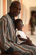 Chernor Anhusine Barrie looks after 20-month-old Naomi Bangura, a malnourished child, while the girl's mother has gone to get lunch at the therapeutic feeding center of the Megbenthe hospital in Makeni, Sierra Leone, on Friday February 27, 2009. UNICEF sponsored some of the construction of the facilities, and also provides high-protein biscuits and milk as part of a joint effort with the World Food Programme.