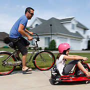 Sam Hornish Jr., a race car driver who has previously raced Indy Car and NASCAR, races around the driveway with daughter Addison, 10, in front of his home in Napoleon, Ohio, on Thursday, June 7, 2018.  He is currently not racing, and is able to spend more time with his kids. Although he tried to convince his kids to race around the driveway counterclockwise so they'd be making left turns, like during a stock car race, the kids chose to keep going clockwise. THE BLADE/KURT STEISS