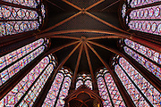 View from below of the choir of the upper chapel of La Sainte-Chapelle (The Holy Chapel), 1248, Paris, France. The upper chapel has four bays and a seven section choir. Each window group has four lancets topped by three rose windows. In the choir, the windows have only two lancets. Fifteen huge mid-13th century windows fill the nave and apse. La Sainte-Chapelle was commissioned by King Louis IX of France to house his collection of Passion Relics, including the Crown of Thorns, and is considered among the highest achievements of the Rayonnant period of Gothic architecture. Picture by Manuel Cohen