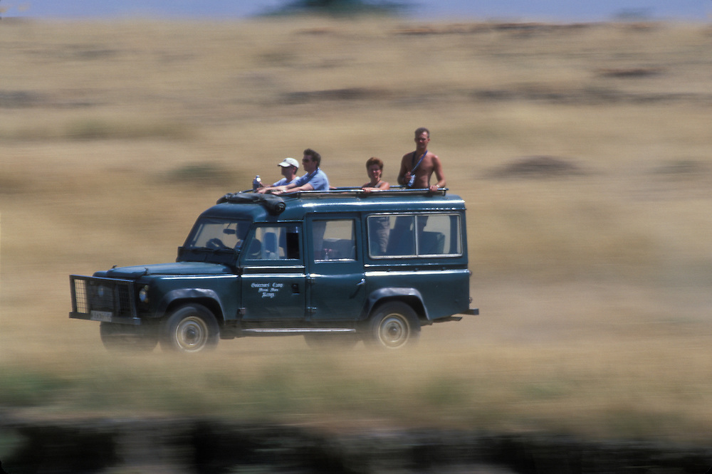 Africa, Kenya, Masai Mara Game Reserve, Blurred image of tourists in safari truck during game drive on savanna