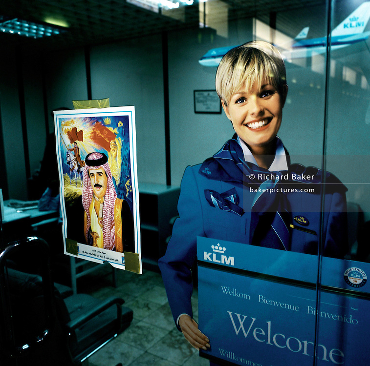 Alongside the official portrait of a member of the Bahraini royal family, the smiling face of a blonde Dutch KLM airline girl adorns a poster in the airline's office in Bahrain airport. This European airline is showing the greatest of respect to the ruling classes in this Gulf State. Similar portraits of kings and princes are seen throughout the arab world, especially where business is being conducted and contracts being sought. Koninklijke Luchtvaart Maatschappij N.V. (KLM Royal Dutch Airlines), known by its initials KLM, is the flag carrier airline of the Netherlands. KLM's headquarters is in Amstelveen near its hub at Amsterdam Airport Schiphol. KLM operates worldwide scheduled passenger and cargo services to more than 90 destinations. It is the oldest airline in the world still operating under its original name.