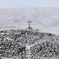 Crucifix standing above the road leading to the Oberalp Pass (2044m) linking Uri and Graubunden Cantons in the Swiss Alps, shortly before the road link closes for months. The area belonged to the National Redoubt, the final Swiss line of defence in the high alps, and is checkered with the remains of millitray installations, many of them underground, still camouflaged.