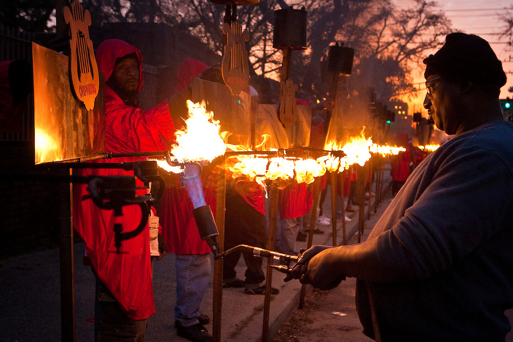 One of the oldest traditions of Mardi Gras, Flambeaux carrying burning kerosene torches line up before parading in the Krewe of Orpheus Parade in the Uptown area of New Orleans, Louisiana, USA.