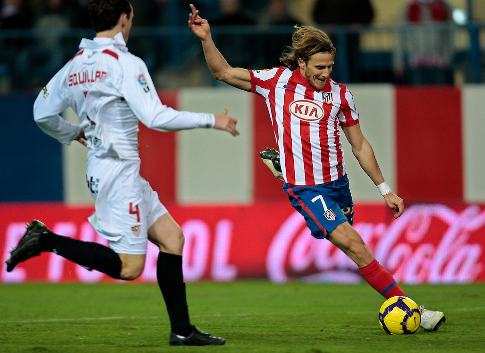 Atletico de Madrid's Diego Forlan from Uruguay, right, vies for the ball with Sevilla's Sebartien Squillaci from France, left, during their Spanish La Liga soccer match at the Vicente Calderon stadium in Madrid, Saturday, Jan. 2, 2010.