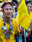 05 MAY 2104 - BANGKOK, THAILAND:  An anti-government protester with religious amulets at an anti-government pro-monarchy rally in Bangkok. Thousands of Thais packed the area around Sanam Luang and the Grand Palace Monday evening for a special ceremony to mark Coronation Day, which honored the 64th anniversary of the coronation of Bhumibol Adulyadej, the King of Thailand. Many of the people also support the anti-government movement led by Suthep Thaugsuban. Most of the anti-government protesters are conservative supporters of the monarchy.   PHOTO BY JACK KURTZ