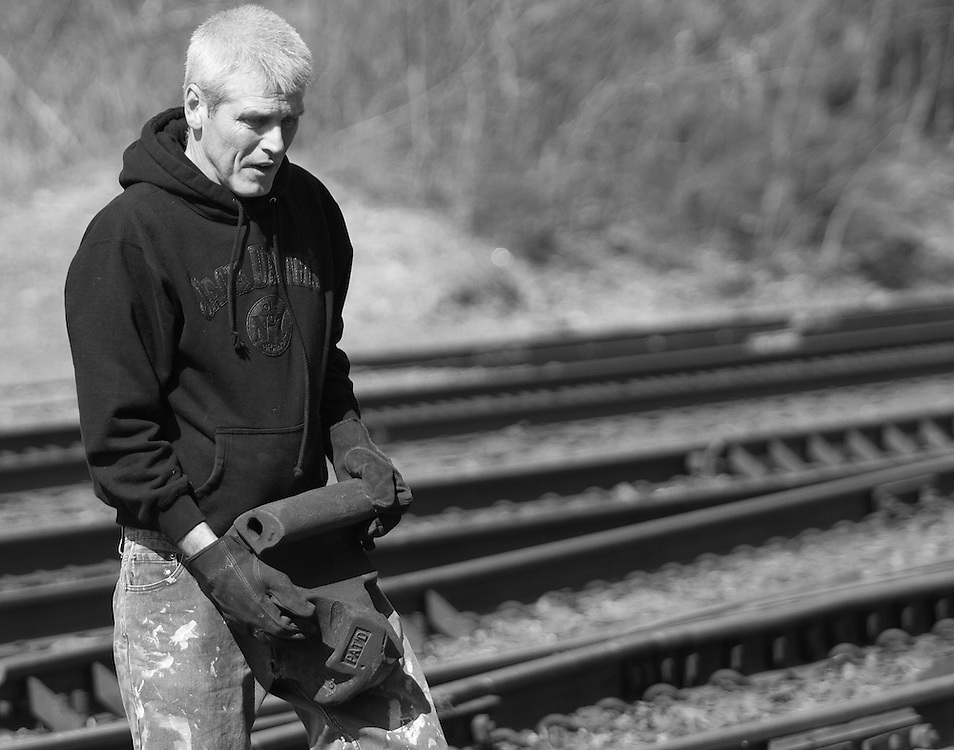 "Brian Croft carries a train knuckle across the tracks. ""Carrying this thing will be part of my training when I start my new job. I'll probably get $20 for this at the metal yard,"" said Croft. (© Matt Wright 2011)"
