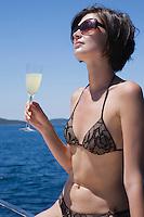 Brunette woman sits on deck in bikini