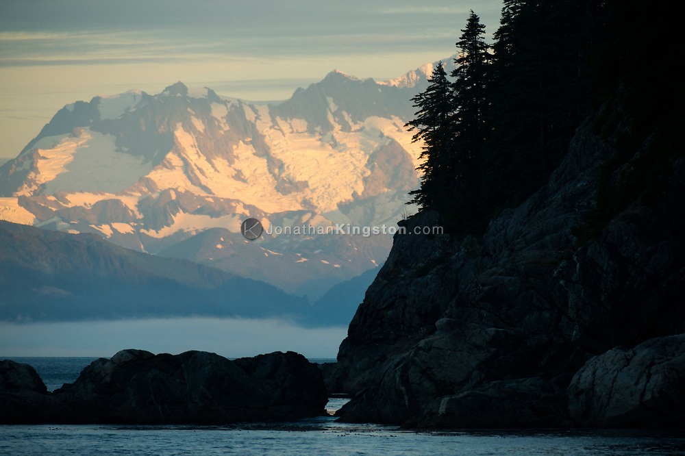 Snow capped peaks that are part of Glacier Bay National park rise above Alaska's inside passage.
