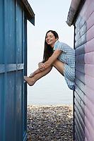 Woman sitting on balustrade of beach house