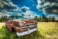 Old Red Plymouth in Grass, Dramatic Sky, Alberta Canada